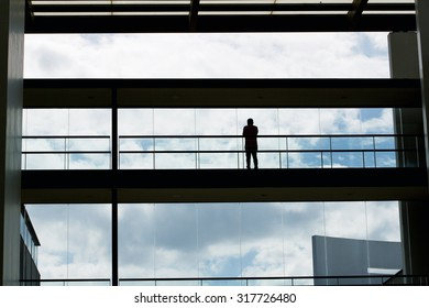 Silhouette view of young businessman walking in modern office building interior with panoramic windows.