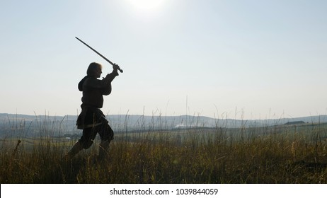 Silhouette of a Viking practicing using the sword for battle. Viking dressed in armor with a helmet on his head. Medieval Reenactment. Contre-jour