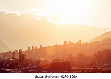 Silhouette of village and mountains at sunset