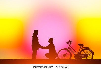 silhouette vintage bike and love couple in  the holiday on blurry colorful sky background.