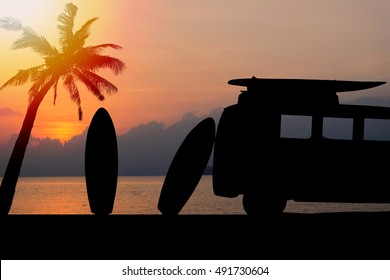 silhouette vintage car in the beach with a surfboard on the roof.