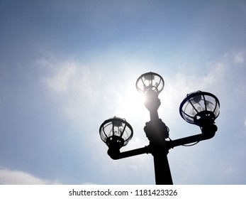 Silhouette of a vintage lamp post against a blue sky.