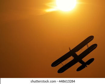Silhouette of vintage single engine propeller biplane aircraft banking left while climbing towards scenic sunset detail close up view