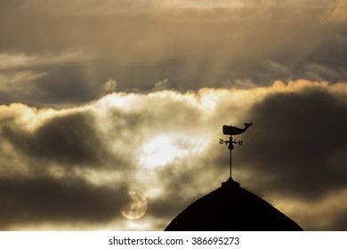 Silhouette of a vintage Whale weather vane with a dramatic moody and cloudy sunset in the foreground.