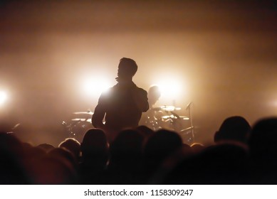 the silhouette of a vocalist and a drummer on the stage of a musical rock festival. audience at the concert. concert photo of musicians.