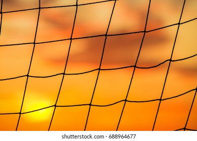 Silhouette of volleyball mesh cells against the orange sunset sky.