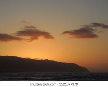Silhouette of the Waianae Mountain Range and Kaena Point against a glowing sky after sunset, as seen from Haleiwa Alii Beach Park in Haleiwa, Hawaii on the island of Oahu