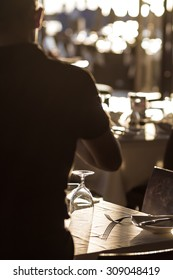 silhouette of a waiter serve banquet tables at outdoor restaurant