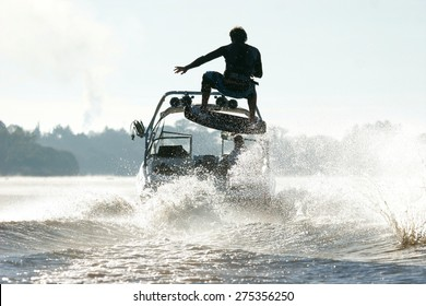 Silhouette of a wake skater as he launches off the wake behind a boat.