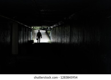 silhouette of a walking man at the end of the tunnel, in the hands of men bags and packages, background road pedestrian and trees