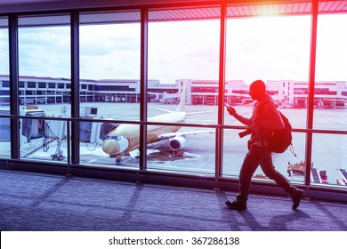 Silhouette of walking  man with smartphone at generic international airport terminal -  Traveling person with bag inside gate ready to flight - Tilted composition with modified paintings on the plane