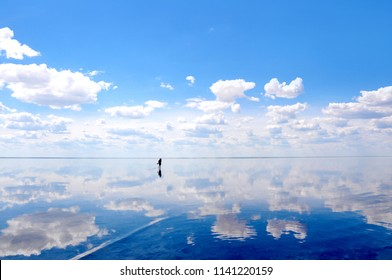 Silhouette walking on the calm water of the lake Elton, the biggest salt lake in Europe, with amazing mirror reflections of sky and clouds, Russia, Volgograd oblast