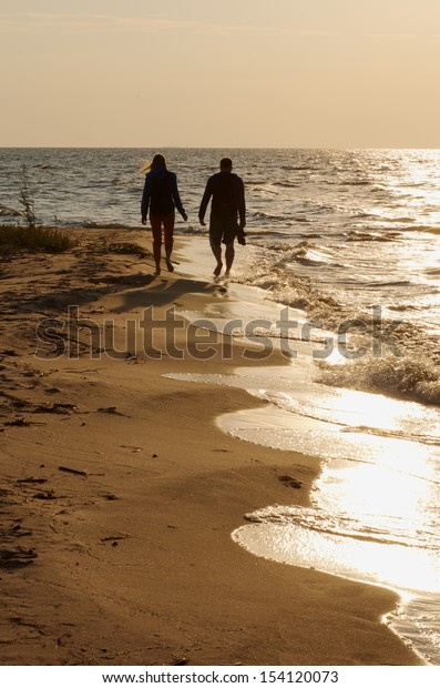 Silhouette of walking young couple by the sea on golden sunset with the calm sea background, multicolored sunset and man and woman walking near the sea, two people in love in sunset time, lovers