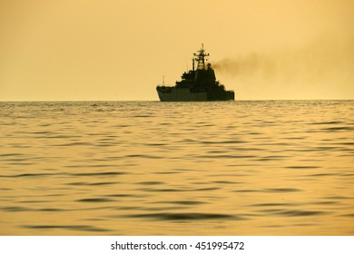 silhouette of a warship at sea