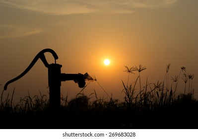 The silhouette water pump on the grass and rice field with the sun on the evening copy space
