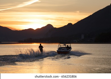 Silhouette of a water skier in sunset background