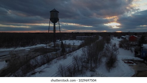 Silhouette of water tower and sunset rays shining through clouds