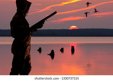 silhouette of a waterfowler at sunset background on the waterfowl hunting