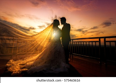 silhueta de casamento Casal no amor beijando e segurando a mão juntos durante o pôr do sol com fundo do céu à noite