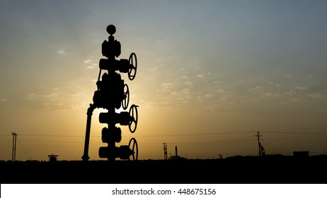 Silhouette of wellhead assembly on oil well in oilfield