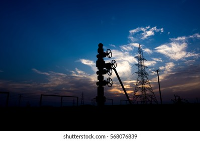 Silhouette of wellhead of a oil well in oil field at sunset blue hour