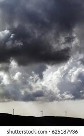 Silhouette of wind farm and cloudy sky before storm. Turkey, coast of Marmara.