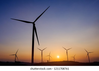 Silhouette wind turbine field generate of electrical with sunset sky background