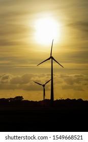 silhouette of wind turbine with sunrise