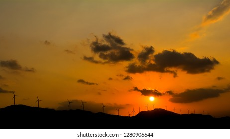 Silhouette of wind turbines against sunset sky with puffy clouds. Panoramic view of a windmill farm, Karnataka, India.