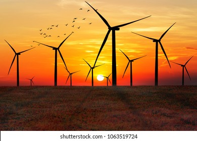 Silhouette of wind turbines at sunset. The concept of alternative energy.