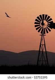 Silhouette of windmill, bird, and California hills.