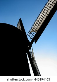 Silhouette of windmill blades against blue sky