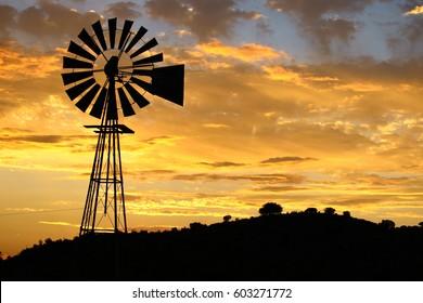 A silhouette of a windmill in the Karoo at sunset.