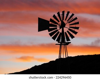 Silhouette of a windmill on a hill against an cloudy orange sunset sky