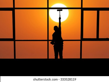 silhouette of a window washer washing a window on sunset background