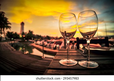 Silhouette of a wine glass on the dinner table blurred lighthouse and sunset background