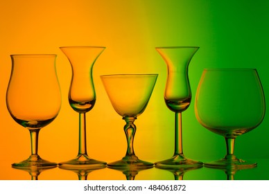 silhouette of wine glasses on orange and green background with space for text