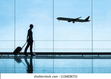 silhouette of woman in airport traveling with luggage suitcase, travel and tourism concept, airplane tickets