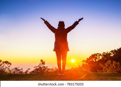 Silhouette of woman arms up outstretched for praying with sunbeam on hill. Christian praise on hill at sunset.