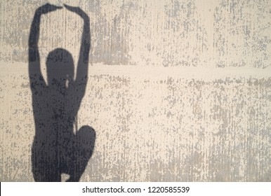 Silhouette of woman with arms up posing like a ballet dancer against decayed wall in sunlight. Copyspace.