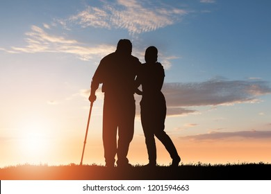 Silhouette Of Woman Assisting Her Disabled Father Walking In Park At Dusk