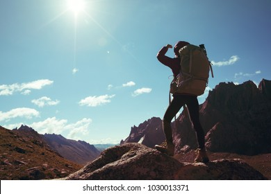 silhouette of woman with backpack hiking on sunrise mountain top