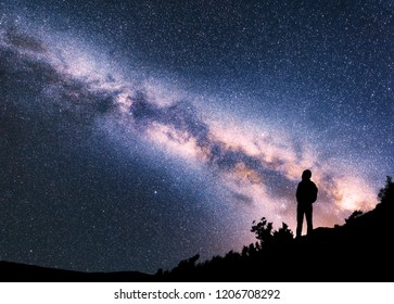 Silhouette of woman with backpack on the hill against colorful Milky Way at night. Space background. Landscape with girl, bright milky way, sky with stars. Amazing galaxy. Travel in Nepal. Starry sky