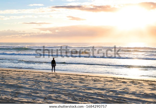 Silhouette of a woman at the beach watching the sun rise over the ocean as waves break.