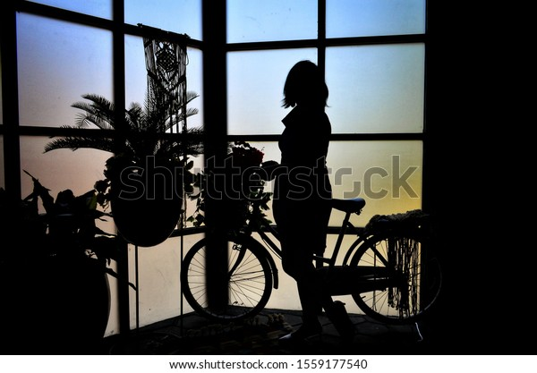 Silhouette of a woman and bicycle by the window.