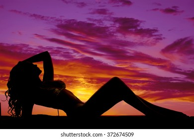 A silhouette of a woman in a bikini laying in the sunset.