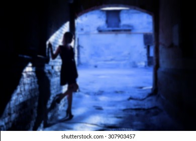 The silhouette of a woman in a black alley (blurred background)