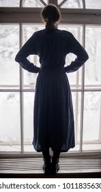 Silhouette of a woman in the blue dress looking at the window