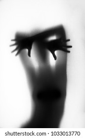 silhouette of a woman body through glass