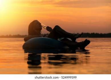 Silhouette of a woman with champagne on inflatable ring in water at sunset